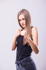 Portrait of young sport girl training boxing against grey background.