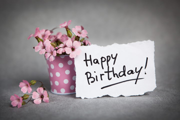 Happy birthday words with pink flowers on gray background