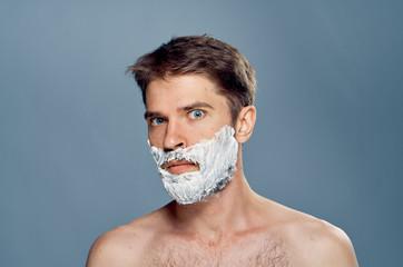 Man in shaving foam against a gray background, portrait
