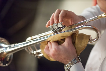 music, jazz, art concept. there is the most popular jazz instrument, trumpet, in old groomed hands of male professional player, he has simple but shiny silver wristwatch on the left hand