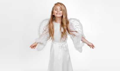 Gracious little girl, blonde, little princess dressed in an angel outfit consists handles prayer in  white Communion or merry christmas dress