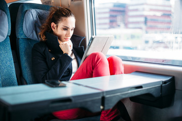 Millennial young woman using tablet computer train traveling