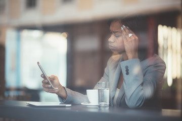 Serious young black businesswoman texting in coffee shop