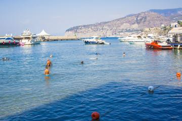 Persone si fanno il bagno a largo della spiaggia libera nella marina piccola di Sorrento. L' acqua è pulita e limpida nonostante le barche e gli yacht a largo della costa. In fondo un promontorio.