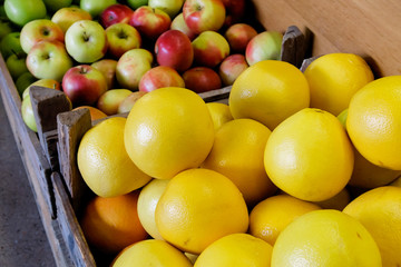 Wooden rustic boxes with grapefruit and apples.