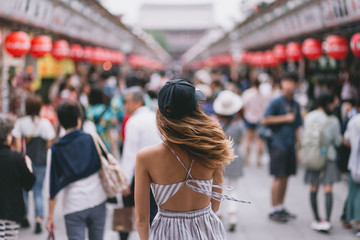 Backview of young hipster woman on the streets of Japan