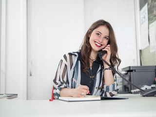 Cheerful young woman is talking on the phone while working at her office
