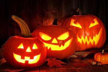 Halloween night scene with a group of spooky Jack o Lanterns against a wood background