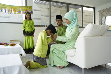 Two children seeking forgiveness from their parents over Hari Raya