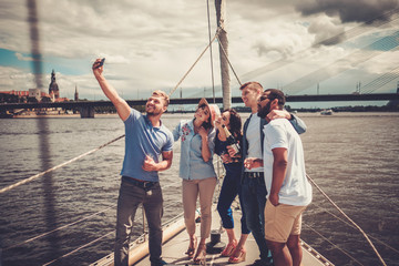 Happy friends taking selfie on a yacht