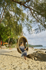Woman sits in hanging basket chair on beach