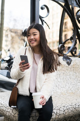 Chinese young woman using her smartphone in the street and smiling