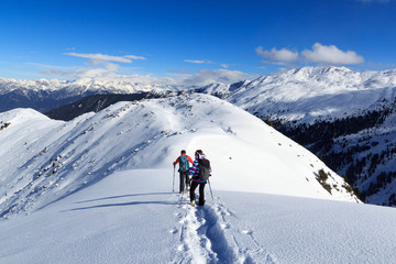 Man and woman hiking on snowshoes and mountain snow panorama with blue sky in Stubai Alps, Austria