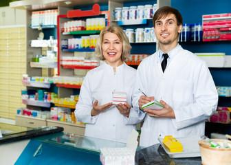 Portrait of two pharmacists working in modern farmacy