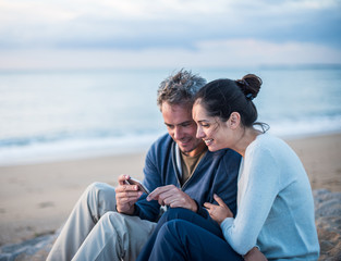 A couple sitting at the beach, looking at photos on a phone