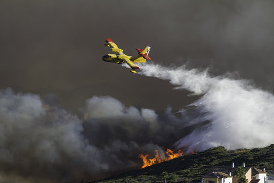 Wild fire close to houses being fought with airplanes and helicopters
