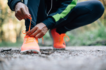 Young black woman runner tying sport shoes