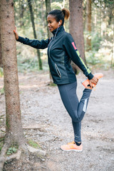 Young black millennial woman stretching in the woods