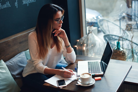 Young and smart. Beautiful young woman work in caffe. Woman writing and using laptop while sitting in restaurant