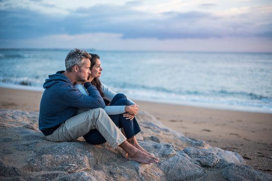 Beautiful couple sitting at the beach watching the sunset