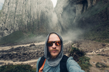 Young Man Traveler Makes Selfie On  Background Of Waterfall And Mountains In Summer