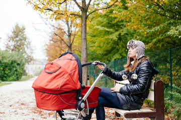 Young woman mother sitting on park bench rocking baby stroller