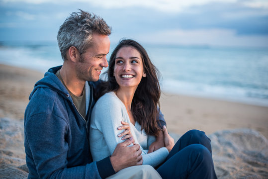 Beautiful couple sitting at the beach watching the sunset