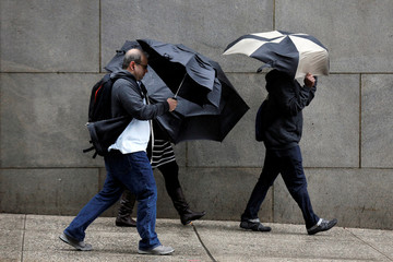 Morning commuters fight through the wind and rain in New York