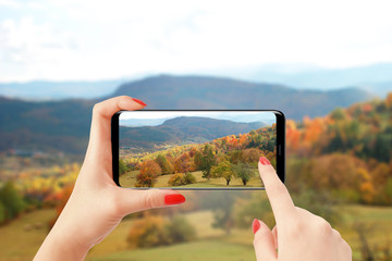 Female hands holding smartphone and taking picture of hills and forest in autumn