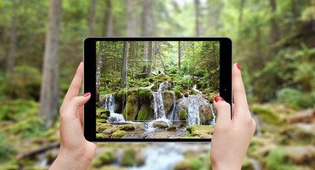 Girl with tablet taking photo of waterfall in woods
