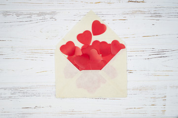 Red hearts in an envelope on a white wooden background