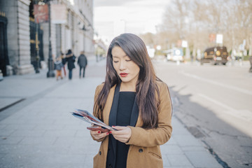Chinese woman walking around Plaza Ramales looking at her maps of Madrid