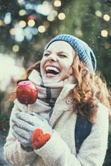 Frau mit Weihnachtsapfel auf dem Weihnachtsmarkt