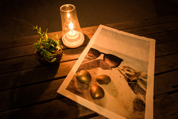 Candle ,Dave plant ,Golden shell and sea picture on the table at romantic night.