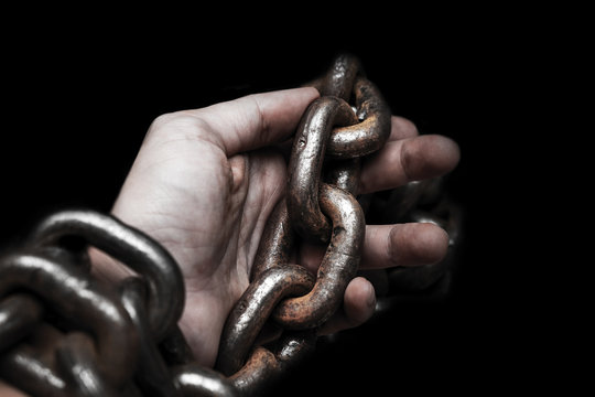 victim, slave, prosoner male hands tied by big metal chain by him self. People have no freedom concept image.