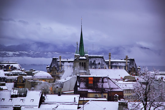 Winter evening in Lausanne. Skyline of Lausanne, Switzerland as seen from the Cathedral hill at sunset zoomed-in on the tower of St-Francois Church.