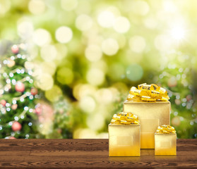 Golden presents on wood table top with christmas tree blurred bokeh light, Mock up for adding your content.