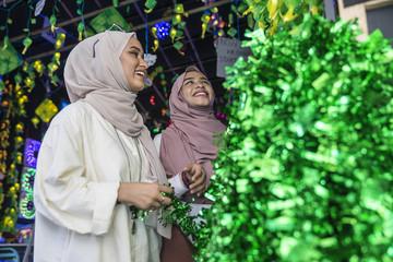 Two muslim ladies shopping for hari raya decorations