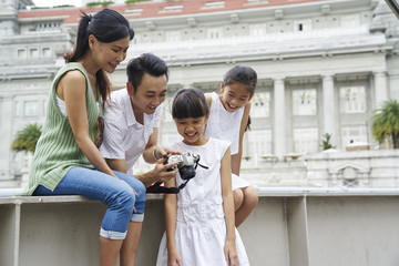 Close-knit Happy family reviewing the images they took at Cavenagh Bridge, Singapore