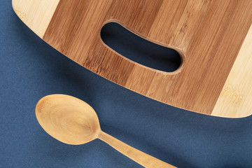 kitchen cutting board and a wooden spoon on a blue