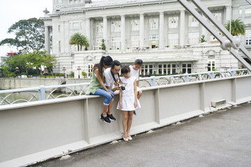 Cheerful family reviewing the images they took at Cavenagh Bridge, Singapore