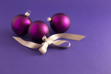 Beautiful purple christmas balls with satin effect and gray gift ribbon on purple background.