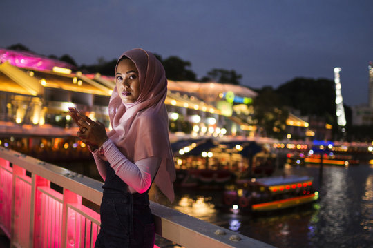 Young Lady Using Her Mobile Phone In The Street, Night Light Background