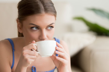Headshot portrait of young woman with porcelain white cup in hands drinking coffee, looking in window after wake up. Pretty lady enjoying fresh brewed invigorating drink with caffeine relaxing in cafe