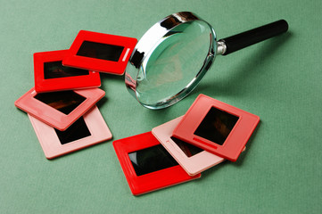 old slides and a magnifying glass on green table