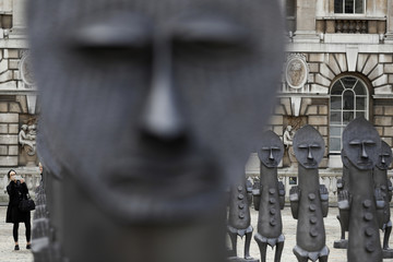 "A woman photographs the sculptures ""Black and Blue: The invisible Man and the Masque of Blackness"", by artist Zak Ove, at Somerset House in London"