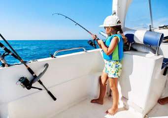 Little girl with a fishing rod fishing from the boat