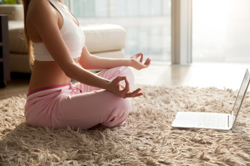 Close up image of slim woman meditating on floor in living room in front of laptop. Young lady sitting in lotus position on soft carpet at home, practicing on spiritual session, struggling with stress