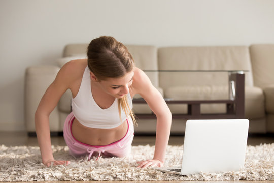 Young fit woman in sportswear watching online video with fitness exercises on laptop and doing push ups at home. Pretty lady burning calories, practice pilates. Distant training with personal trainer