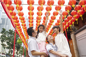 Happy family of four having fun with Chinese New Year decorations